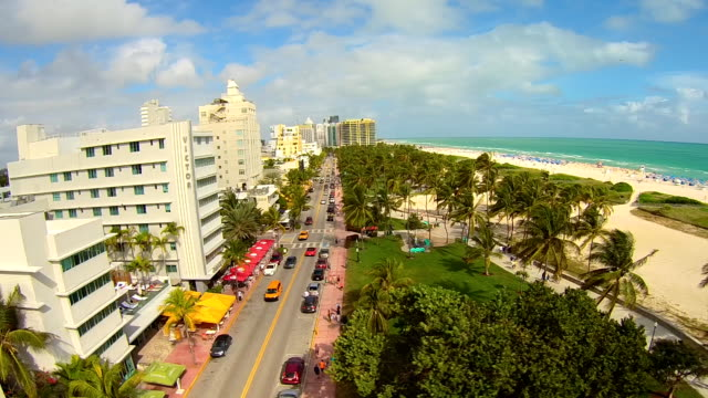 Aerial side 'dolly' view low over miami south beach, looking from Ocean Drive trees to ocean.