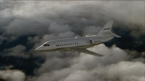 aerial side view of corporate jet flying through cloudy sky - air to air shot stock videos & royalty-free footage