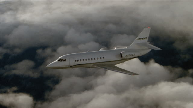 aerial side view of corporate jet flying through cloudy sky - flugzeug in der luft stock-videos und b-roll-filmmaterial