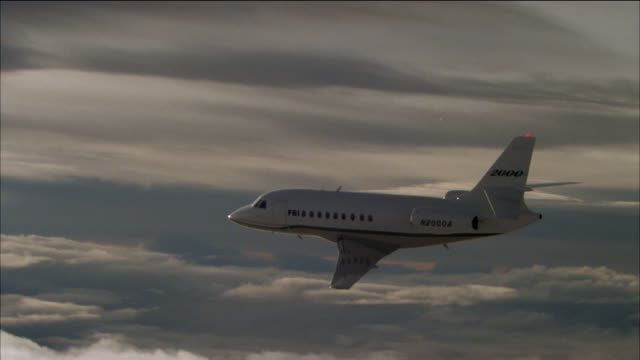aerial side view of corporate jet flying through cloudy sky - side view stock videos & royalty-free footage