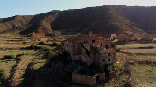 aerial sidewards around cluster of derelict houses in hilly tree landscape in abandoned village el campo, aragon - spanien stock-videos und b-roll-filmmaterial