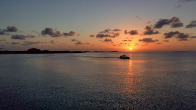 aerial: silhouette of boat sailing past orange beach sunset - providenciales, turks and caicos - 島点の映像素材/bロール