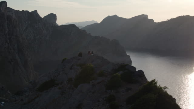 aerial: silhouette people hiking while sitting on mountain peak by sea against sky during sunset - mallorca, spain - majorca stock videos & royalty-free footage