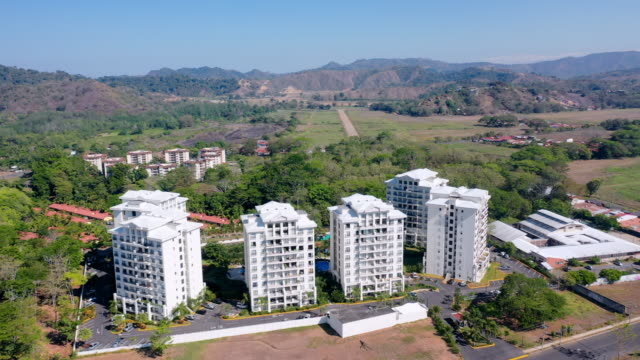 aerial: six tall buildings towering over city of jaco near beach with vibrant tropical water - nummer 6 bildbanksvideor och videomaterial från bakom kulisserna