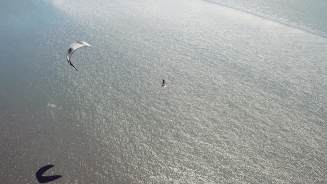 UHD 4K Aerial: Skilled kite surfer blazing through Alaskan waters with gorgeous mountains as a backdrop