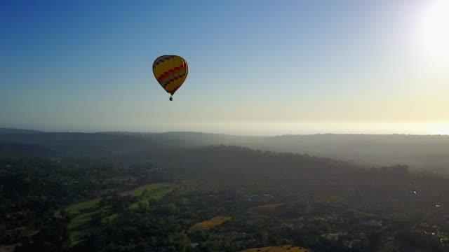 vídeos y material grabado en eventos de stock de aerial: slow circle of yellow hot air balloon - globo aerostático