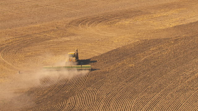 aerial slow motion a dust cloud billows from a bulldozer pulling a large disc turning the soil in a dry barren agricultural landscape. - hay field stock videos & royalty-free footage