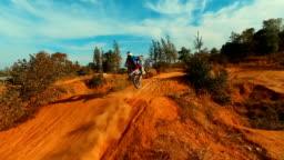 Aerial: Slow motion jump on motocross track.