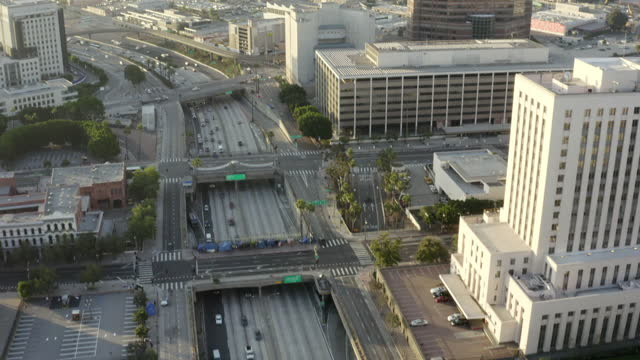 aerial slow motion panning of the santa ana freeway in downtown la with surrounding buildings under a bright sky and the city suburbs stretching into the distant hazy horizon - los angeles, california - courthouse stock videos & royalty-free footage