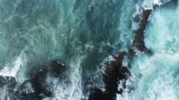 Aerial Slow Motion Shot Of Waves Rushing Towards Rocky Shore