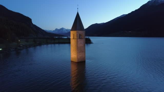aerial: slow pan of the famous lake reschen bell tower at night between hills and mountains - south tyrol, italy - tornspira bildbanksvideor och videomaterial från bakom kulisserna