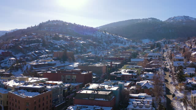aerial slow tilt up over a residential neighborhood in a snowy mountain ski town with quiet streets and bright morning sunlight - park city, utah - park city stock videos & royalty-free footage