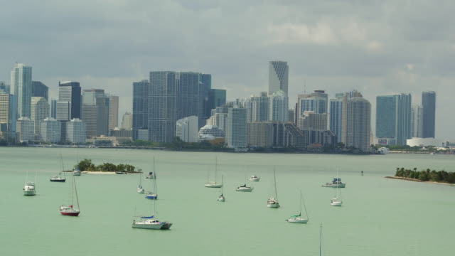 aerial slowly floating over sailboats anchored in the water toward the miami skyline - anchored stock videos & royalty-free footage