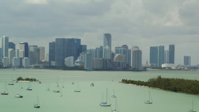aerial slowly floating over sailboats anchored in the water with the miami skyline in the background - anchored stock videos & royalty-free footage