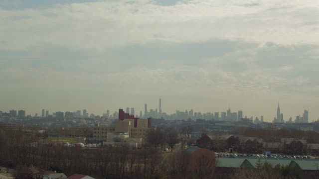 Aerial slowly moving toward New York City skyline from New Jersey suburbs