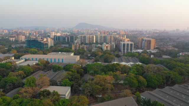 aerial: slum by modern buildings against sky - mumbai, india - インド点の映像素材/bロール