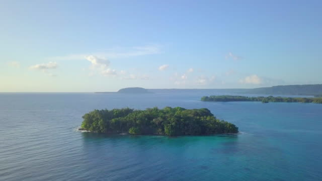 aerial: small island in the calm blue ocean in espiritu santo, vanuatu - pacific ocean stock videos & royalty-free footage