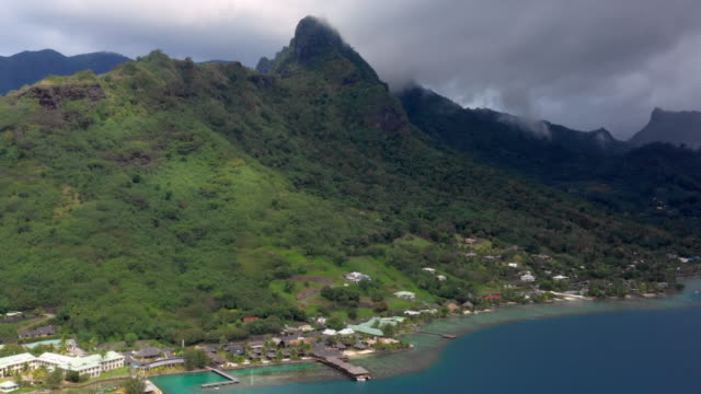 stockvideo's en b-roll-footage met aerial: small town on the coastline of moorea with mountains on the other side, moorea, french polynesia - overige