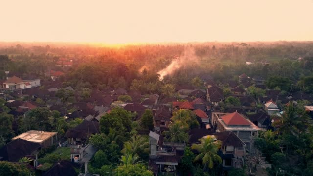 aerial: smoke floating in beautiful sunset in lush green tropical town - indonesia stock videos & royalty-free footage