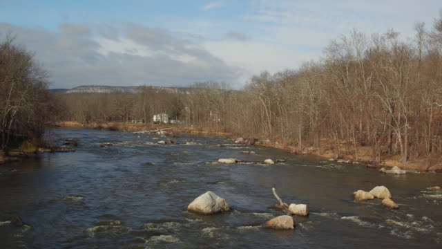 aerial soaring along river lined with trees in winter - new paltz stock videos and b-roll footage