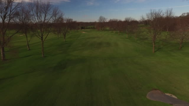 aerial soaring low over golf course on sunny autumn day - golf flag stock videos & royalty-free footage