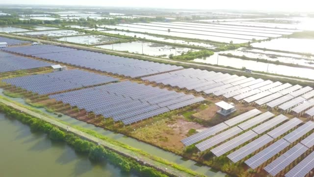 aerial solar power station or solar panel row at sunset fly over shot and reflection near local road and lake in south east asia - power in nature stock videos & royalty-free footage