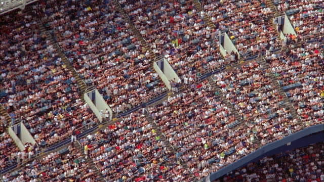 aerial spectators in stands at baseball stadium / zoom out stadium and surrounding area / new york city - baseball sport stock videos & royalty-free footage