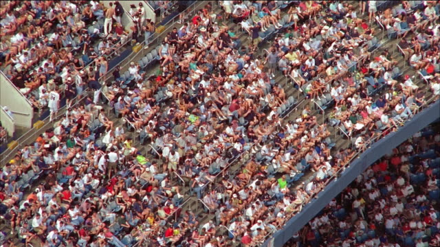 aerial spectators in stands at baseball stadium / zoom out stadium and surrounding area / new york city - new york yankees stock-videos und b-roll-filmmaterial