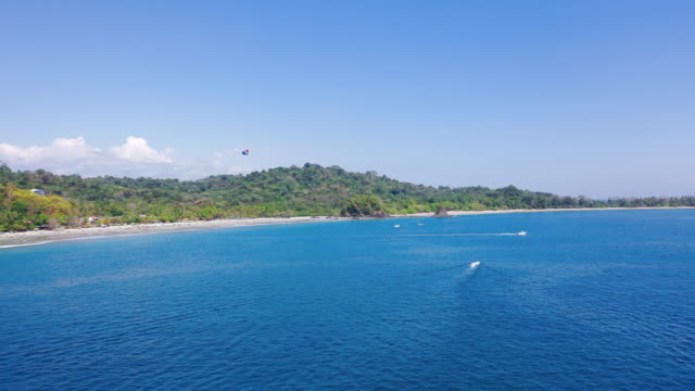 aerial: speedboat, jet ski and parasailing on beautiful blue ocean on a sunny day - playa espadilla, costa rica - barca a motore video stock e b–roll