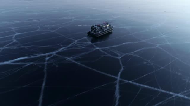 aerial: speedy hovercraft travels on lake baikal at dusk - hovercraft stock videos & royalty-free footage