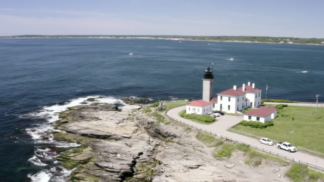 aerial spin: a lighthouse building above waves crashing on rocks - newport, rhode island - new england usa stock videos & royalty-free footage