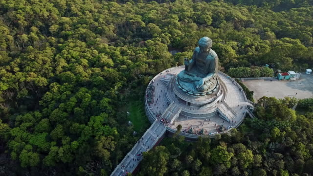 aerial spin: large statue of tian tan buddha tourists are visiting - tian tan buddha stock videos and b-roll footage