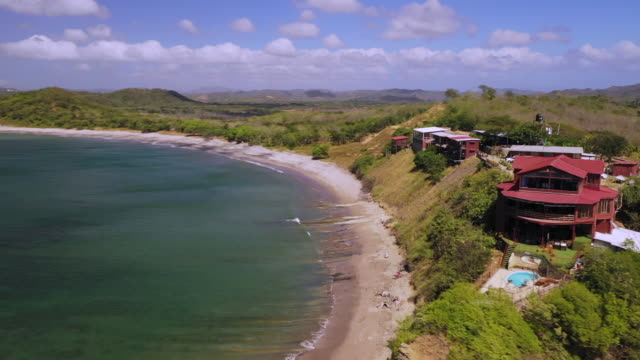 aerial spin right: large, red house on grassy plain by shore of vibrant ocean  - el gigante, nicaragua - bay of water stock videos & royalty-free footage