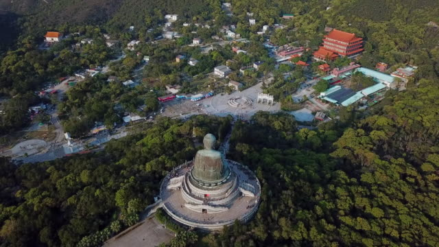 aerial spin: the back of tian tan buddha statue in a forest - tian tan buddha stock videos and b-roll footage