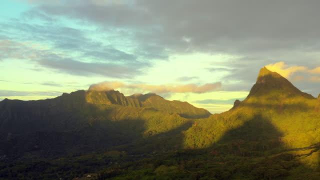 vidéos et rushes de aerial spin: the sun shines partially on the mountains as it rises in moorea, moorea, french polynesia - moorea