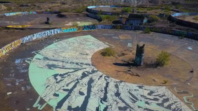 aerial spinning: artwork in half of a circular object - zement stock-videos und b-roll-filmmaterial