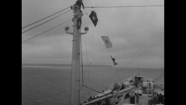 aerial ss united states in harbor at le havre france / passengers on deck pan to us flag and other flags mounted on the radar mast / ls down int... - イングランド サウサンプトン点の映像素材/bロール