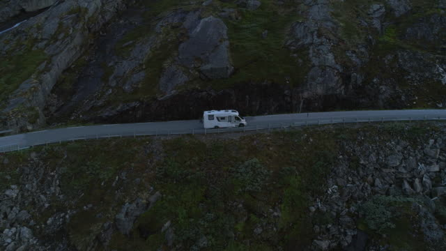 aerial: stationary camper van on winding road by rocky mountain - dalsnibba mountain plateau, norway - van stock videos & royalty-free footage