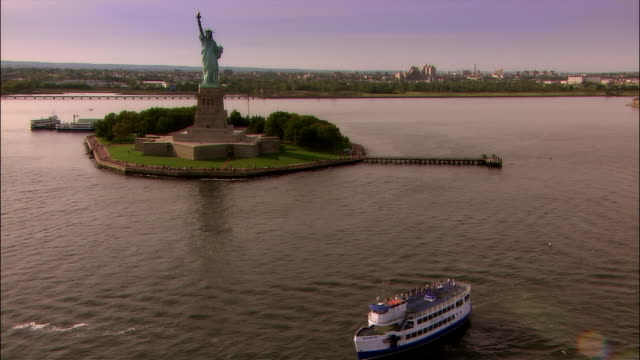 aerial statue of liberty, liberty island, and tourboat in new york harbor/ new york city - tourboat stock videos and b-roll footage