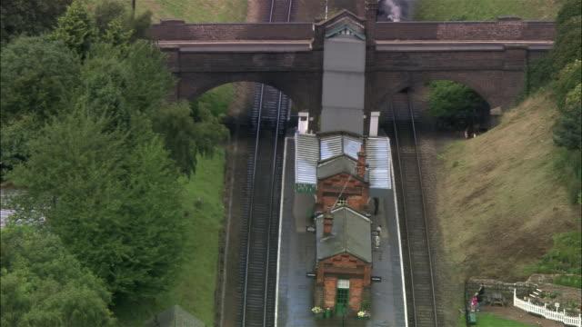 vídeos de stock, filmes e b-roll de aerial steam locomotive pulling into station on great central railway / leicestershire, england - forma da água