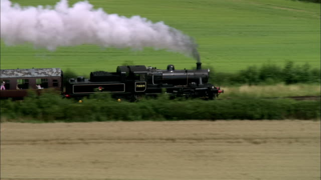 aerial steam locomotive traveling through countryside on great central railway / england - locomotive stock videos & royalty-free footage