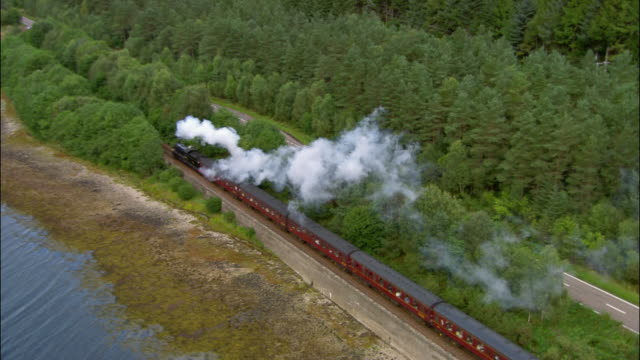 Aerial steam train traveling along shore of Loch Eil / next to empty highway / Scotland