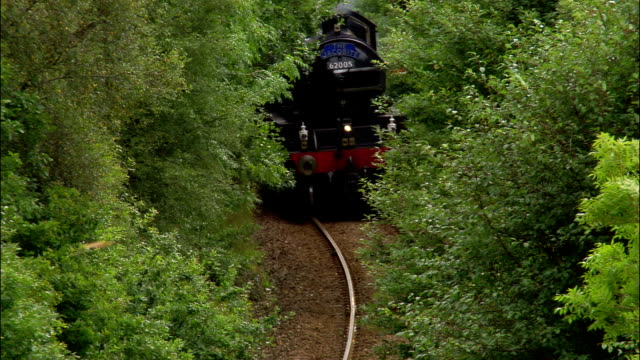 aerial steam train traveling through stand of trees alongside highway towards loch eil / scotland - steam train stock videos & royalty-free footage