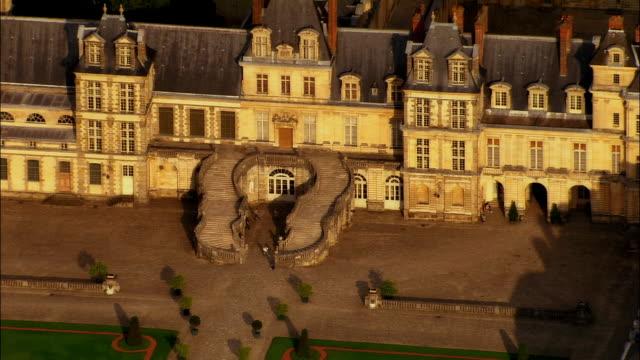 Aerial WS ZO Steps outside Chateau de Fontainbleau near landscaped gardens and surrounding cityscape / Seine-et-Marne, Ile-de-France, France