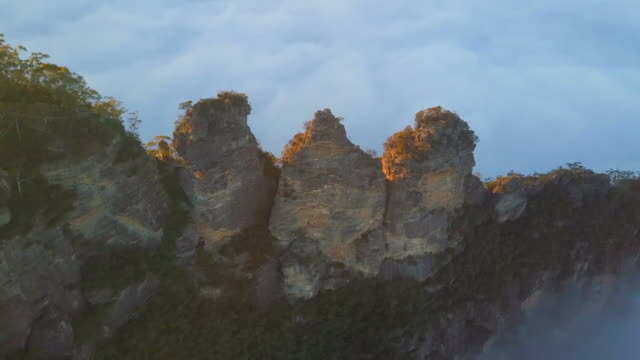 aerial: stunning famous three sisters rock formation in thick clouds, blue mountains, australia - ニューサウスウェールズ州点の映像素材/bロール
