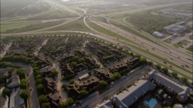 Aerial suburban development next to motorway/ over motorway junction and traffic/ following traffic on motorway/ Houston, Texas