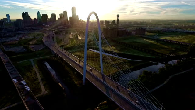 aerial: sun burst through the cables of the margaret hunt hill bridge sunrise over dallas texas skyline cityscape sun burst right above the horizon golden hour - dallas stock videos & royalty-free footage
