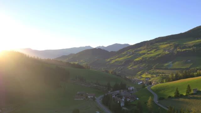 vidéos et rushes de aerial sun flare view alpine forest mountain valley - village
