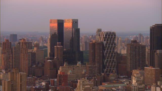 aerial ws zo sun reflecting off time warner center and surrounding midtown cityscape including hearst tower, cityspire center, and worldwide plaza / manhattan, new york, new york, usa - time warner center stock videos & royalty-free footage