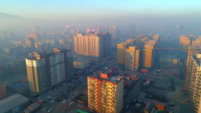 aerial: sun shines on the tall city buildings in ulaanbaatar - ulan bator stock videos & royalty-free footage
